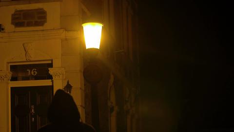man in a hoodie walking in the night in a desert street Footage