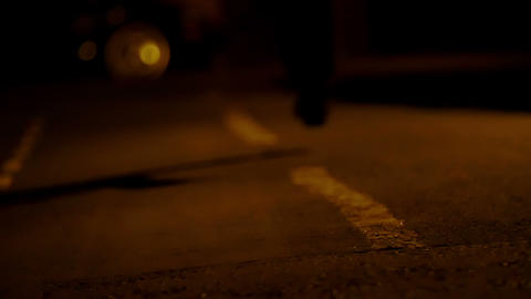 detail of feet of man running alone in the street during the night v Live Action