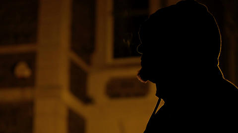 profile a man smoking in the dark, hiding his in a hoodie Footage
