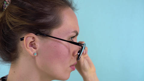 Close-up of a glamorous beauty picks up glasses and puts them back on. Beauty Live Action