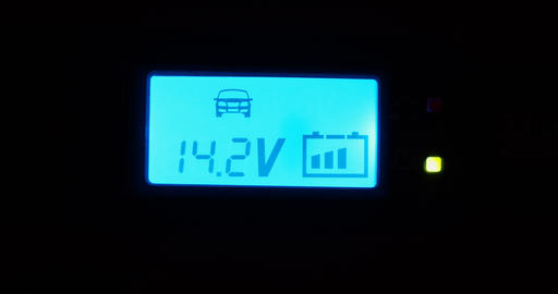 Car battery charger display voltage with blinking battery level - blue led display close-up Live Action