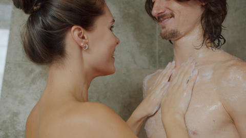 Girl and guy loving couple washing in shower together taking expressing love Live Action