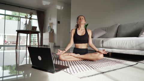 Pretty young woman doing yoga online at home. Healthy lifestyle concept Live Action