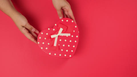 two female hands are holding a red cardboard box in the form of a heart, red table Live Action