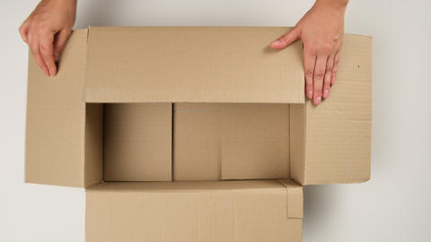 female hand opens brown cardboard box and fills with white filler for safe transportation, top view Live Action