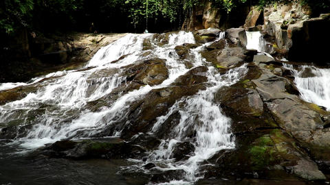 Scenic Kanto Lampo waterfall cascading down a stepped rock in Bali island Live Action
