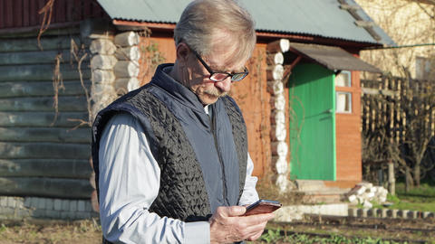 An elderly man in glasses and a blue vest selects information on a smartphone Live Action