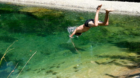 Slowmotion of young man diving on crystal river water,natural scene,freedom Live Action
