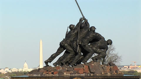 The camera slowly pans-up the Iwo Jima Marine Corps memorial to the American flag Footage