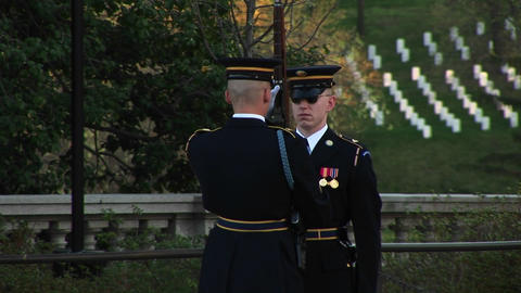 A soldier stands at attention in full uniform as another soldier inspects his gun Footage