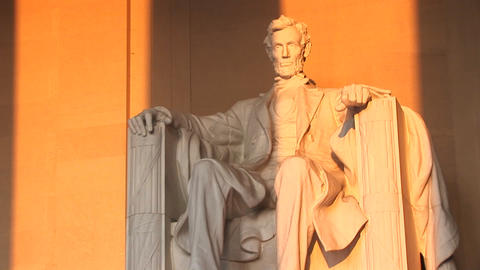 Columns of the Lincoln Memorial Building cast long shadows on the statue seen inside Footage