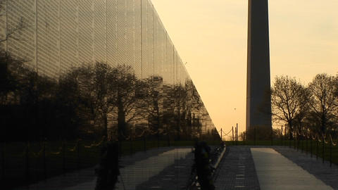 With a golden sky backdrop, the Washington Monument is seen in silhouette next to the Vietnam Memori Footage