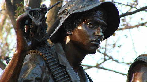 Pan-right to a close-up of the faces of the Three Soldiers sculpture in Washington, DC Footage