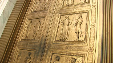 Close view pan-up of the bronze sculptures on the west entrance doors of the Supreme Court Live Action