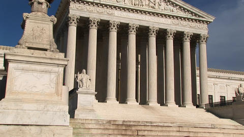Warm sunlight shines on the white stone steps and bright white pillars of the U.S. Supreme Court Bui Footage