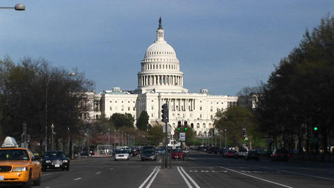 Traffic Flows In Many Directions On The Tree-lined Streets In Front Of The United States Capitol Bui stock footage