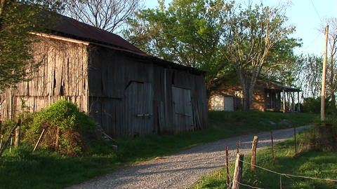 Medium-shot of an old barn next to a dirt road with house... Stock Video Footage