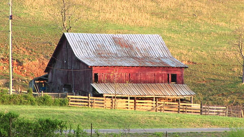 Cars pass by an old abandoned farm shed and lean-to that... Stock Video Footage