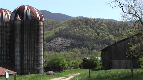 large grain silos and the surrounding mountains dominate the landscape of this rural farm Footage