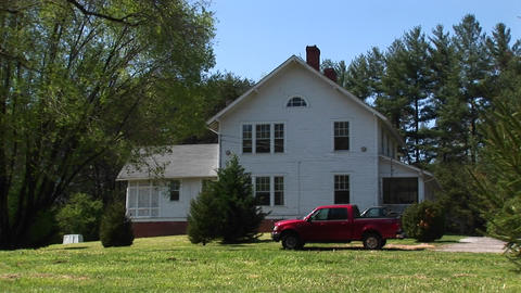 A newer model red pickup sits parked in front of a quaint white farmhouse Footage