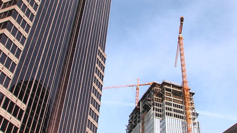 A tilt shot of a skyscraper and new construction in the city of Atlanta Footage