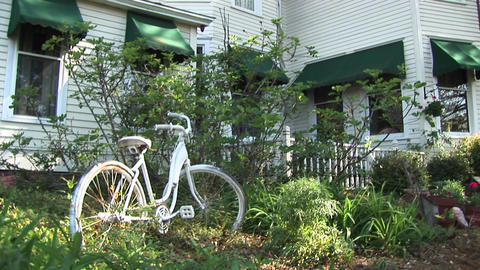 A bike sits in the bushes in front of a double story... Stock Video Footage