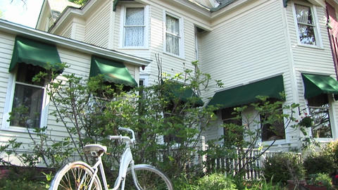 A bike sits in the bushes in front of a double story white house Footage