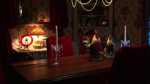Candles sit on a formal dining table under a chandelier Footage