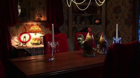 Candles sit on a formal dining table under a chandelier Stock Video Footage