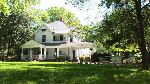A beautiful, two-story country home surrounded by trees... Stock Video Footage