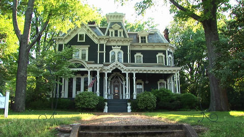 A lovely old house is surrounded by large leafy green trees Stock Video Footage