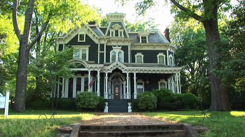 A lovely old house is surrounded by large leafy green trees Footage