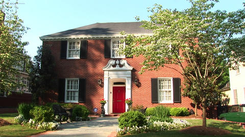 A traditional, red painted door beckons a welcome to this beautiful Colonial Revival home Footage