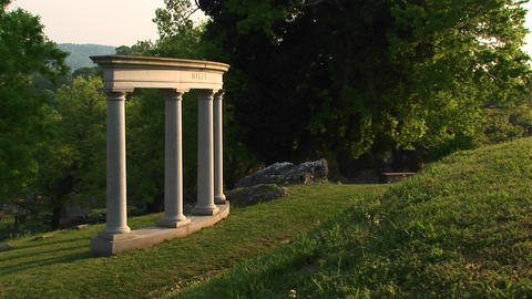 Four stately architectural columns grace a manicured hillside Footage