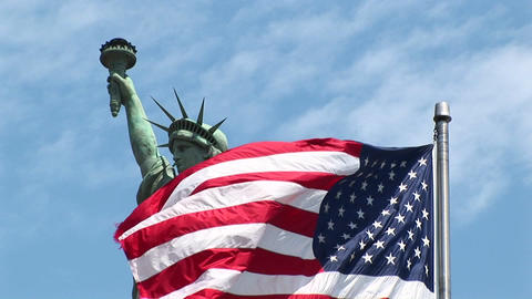 The American flag waves in the foreground with the Statue... Stock Video Footage