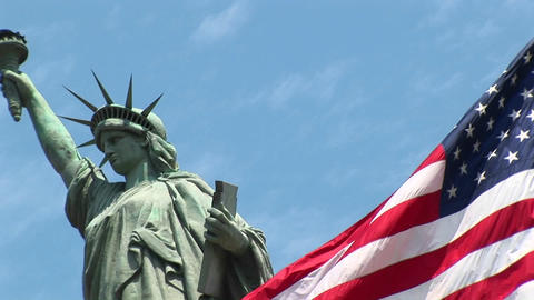 The camera pans-left across a rippling American flag, revealing the Statue of Liberty in the backgro Footage