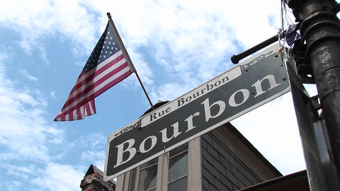 An American flag flies above a street sign identifying New Orleans's famed Bourbon Street Footage