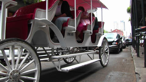 A horse-drawn tourist carriage makes its way down a crowded street in New Orleans Footage