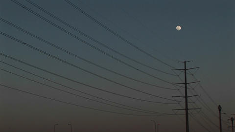 Medium-shot of the moon high above powerline Stock Video Footage