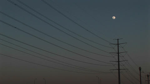 Medium-shot of the moon high above powerline Footage