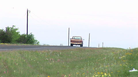 Medium-shot of a pickup truck driving down a two-lane Texas road Footage
