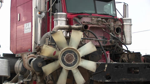 Pan-up from the engine to the exhaust pipe and fan of a red semi-truck cab Footage