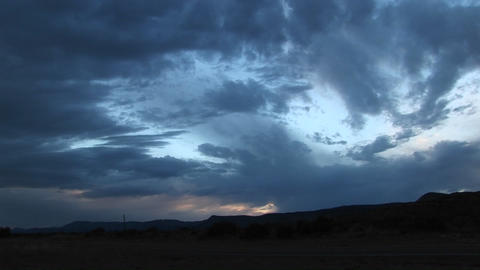 Pan-right shot of storm clouds over a hilly landscape Stock Video Footage