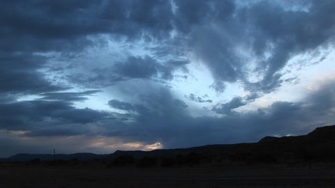 Pan-right shot of storm clouds over a hilly landscape Footage