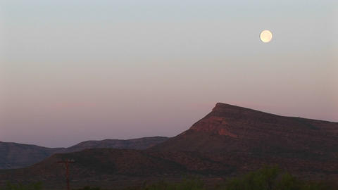 Long-shot of the moon over a rocky landscape Stock Video Footage