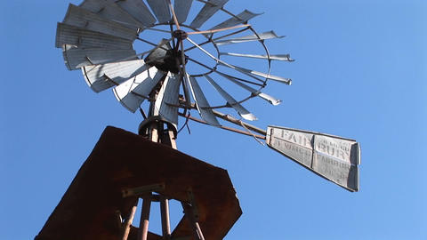 Pan-up from the base of a windmill to the blades turning... Stock Video Footage