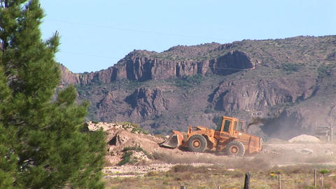 Long-shot of a bull-dozer moving dirt in a desert area Stock Video Footage