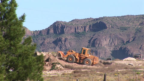 Long-shot of a bull-dozer moving dirt in a desert area Footage