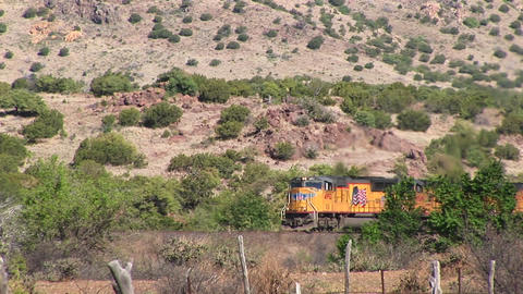 Long-shot of a train crossing over a desert Stock Video Footage