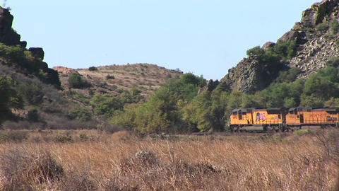 Long-shot of a train passing through a desert canyon Footage